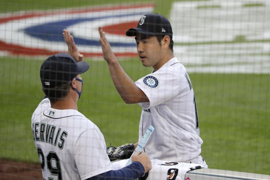 Seattle Mariners starting pitcher Yusei Kikuchi, right, greets manager Scott Servais while heading into the dugout after the top of the sixth inning of a baseball game against the Oakland Athletics, Saturday, Aug. 1, 2020, in Seattle. (AP Photo/Elaine Thompson)