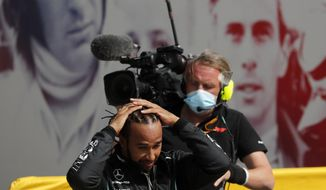 Race winner Mercedes driver Lewis Hamilton of Britain adjusts his hair after getting out of his car after the British Formula One Grand Prix at the Silverstone racetrack, Silverstone, England, Sunday, Aug. 2, 2020. (AP Photo/Frank Augstein,Pool)