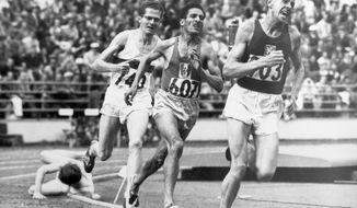 """FILE - In this July 24, 1952, file photo, British athlete Christopher """"Chris"""" Chataway falls as Emil Zatopek of Czechoslovakia, followed by Alain Mimoun of France and German bronze medal winner Herbert Schade, leads near the end of the Men's final 5000 meter race at the Summer Olympic Games on in Helsinki, Finland. (AP Photo/File)"""