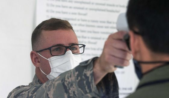 A member of the Nevada National Guard performs a temperature check during the second day of the 32nd Special Session of the Legislature, Saturday, Aug. 1, 2020 in Carson City, Nev.. (David Calvert/Nevada Independent via AP, Pool)