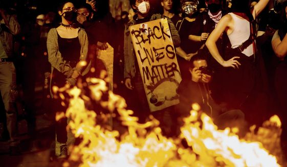 Black Lives Matter supporter Jorge Mendoza holds a sign while rallying at the Mark O. Hatfield United States Courthouse on Saturday, Aug. 1, 2020, in Portland, Ore. (AP Photo/Noah Berger) ** FILE **