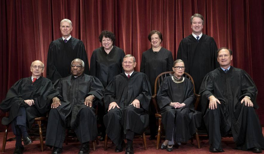 In this Nov. 30, 2018, file photo, the justices of the U.S. Supreme Court gather for a formal group portrait to include a new Associate Justice, top row, far right, at the Supreme Court Building in Washington. Seated from left: Associate Justice Stephen Breyer, Associate Justice Clarence Thomas, Chief Justice of the United States John G. Roberts, Associate Justice Ruth Bader Ginsburg and Associate Justice Samuel Alito Jr. Standing behind from left: Associate Justice Neil Gorsuch, Associate Justice Sonia Sotomayor, Associate Justice Elena Kagan and Associate Justice Brett M. Kavanaugh. (AP Photo/J. Scott Applewhite, File)