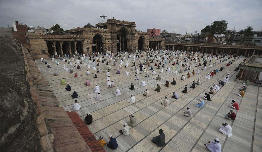 Indian Muslims sit while maintaining social distance and attend an Eid al-Adha prayer service at the Jama Masjid in Ahmedabad, India, Saturday, Aug. 1, 2020. Muslims worldwide marked the the Eid al-Adha holiday over the past days amid a global pandemic that has impacted nearly every aspect of this year's celebrations. (AP Photo/Ajit Solanki)