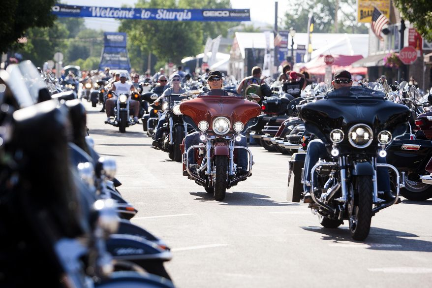 In this Aug. 5, 2016, file photo, bikers ride down Main Street in downtown Sturgis, S.D., before the 76th Sturgis motorcycle rally officially begins.  South Dakota, which has seen an uptick in coronavirus infections in recent weeks, is bracing to host hundreds of thousands of bikers for the 80th edition of the Sturgis Motorcycle Rally. Over a quarter of a million people are expected to rumble through western South Dakota. (Josh Morgan/Rapid City Journal via AP, File)