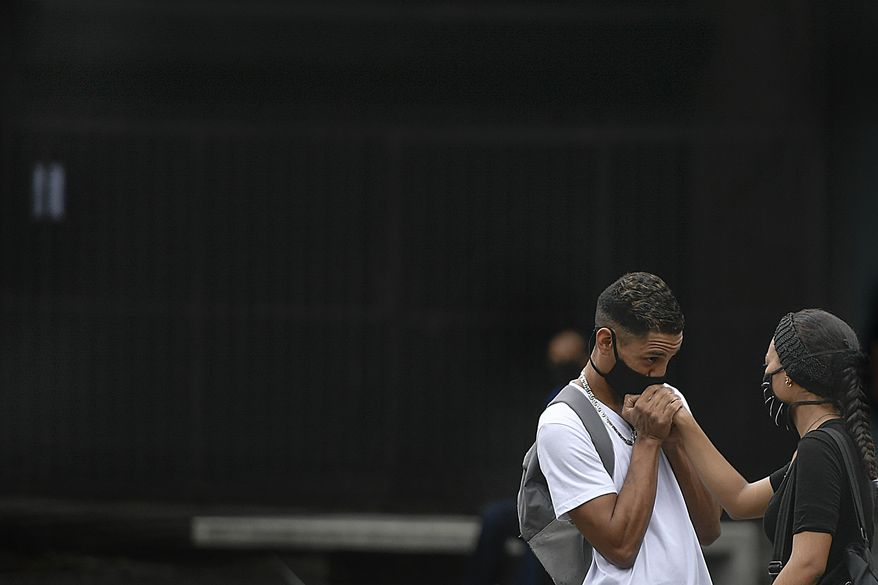 A man, wearing a protective face mask, kisses his girlfriend's hand on Sabana Grande boulevard in Caracas, Venezuela, Saturday, Aug. 1, 2020, amid the new coronavirus pandemic. (AP Photo/Matias Delacroix)