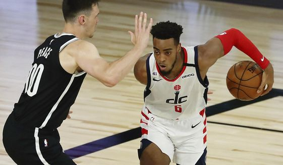 Washington Wizards forward Troy Brown Jr. (6) dribbles in front of Brooklyn Nets forward Rodions Kurucs (00) in the second half  of an NBA basketball game Sunday, Aug. 2, 2020, in Lake Buena Vista, Fla. (Kim Klement/Pool Photo via AP) ** FILE **