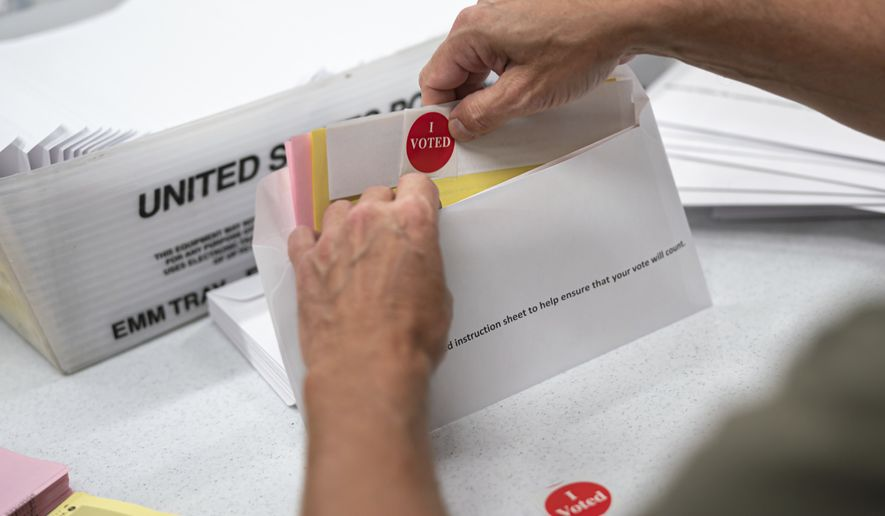 Todd Gallagher prepares mail in ballot envelopes including an I Voted sticker Wednesday, July 29, 2020 in Minneapolis. Absentee ballots are being requested at a record level this year. Nearly 470,000 Minnesotans have requested to vote absentee. That's an amazing 12-times the number requesting mail in voting at this point in 2018. This year's demand obliterates the demand in the 2016 Presidential election, when only 20,000 absentee ballots were requested by July 24.  (Glen Stubbe/Star Tribune via AP)  **FILE**