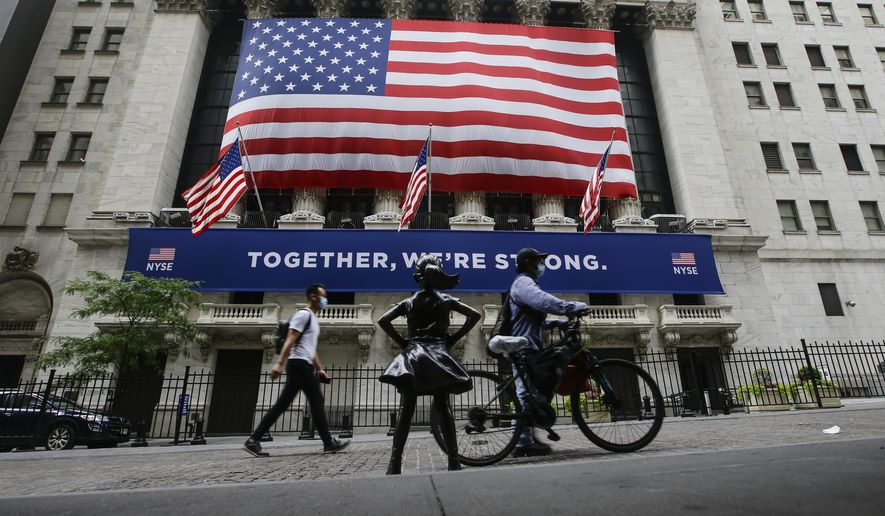 In this Tuesday, July 7, 2020 file photo, pedestrians wearing protective masks during the coronavirus pandemic pass by the New York Stock Exchange in New York. (AP Photo/Frank Franklin II, File)