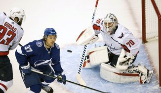 Tampa Bay Lightning center Yanni Gourde (37) and Washington Capitals goaltender Braden Holtby (70) keep a close eye on the puck during the second period of an NHL hockey playoff game  Saturday, Aug. 1, 2020 in Toronto. (Frank Gunn/The Canadian Press via AP)