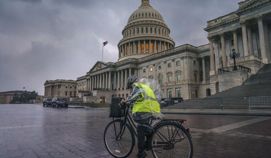 Dark clouds and heavy rain sweep over the U.S. Capitol in Washington, Monday, Aug. 3, 2020, as Tropical Storm Isaias pushes toward the Mid-Atlantic. (AP Photo/J. Scott Applewhite)