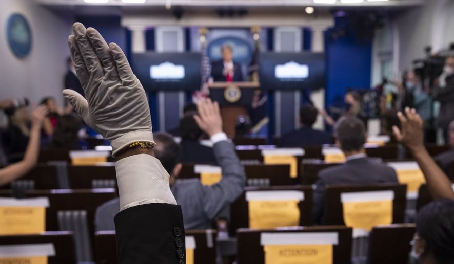 A reporter wearing a glove, raises his hand to ask President Donald Trump a question during a briefing with reporters in the James Brady Press Briefing Room of the White House, Monday, Aug. 3, 2020, in Washington. (AP Photo/Alex Brandon)  **FILE**