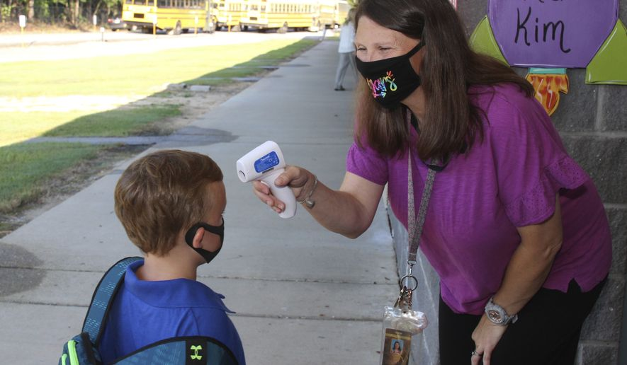 In a photo provided by Newton County Schools, teaching assistant Crystal May talks to kindergarten student Lewis Henry Thompson, 5, as she takes his temperature at Newton County Elementary School in Decatur, Miss., Monday, Aug. 3, 2020. (Janine Vincent/Newton County Schools via AP)