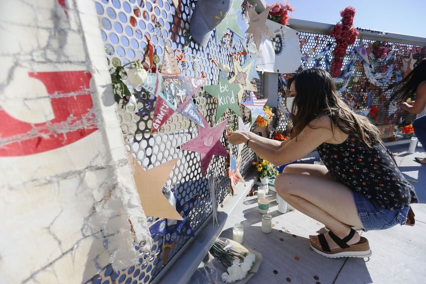Leah Carrasco ties an orange ribbon to the Ponder Park memorial on the one year anniversary of the Walmart mass shooting Monday, Aug. 3, 2020, in El Paso. A gunman opened fire at a Walmart in El Paso killing 23 and injuring several others Aug. 3, 2019.  (Briana Sanchez/The El Paso Times via AP)