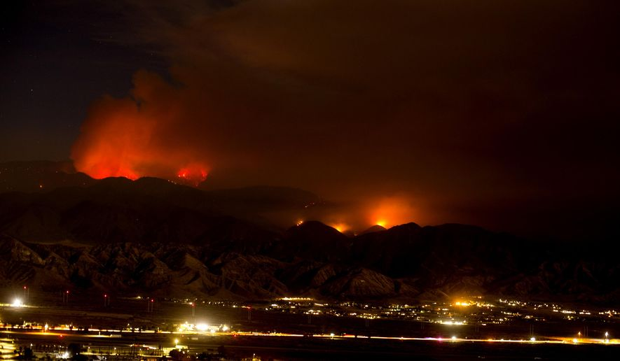 The Apple Fire burns behind mountains near Beaumont, Calif., Sunday, Aug. 2, 2020. (AP Photo/Ringo H.W. Chiu)