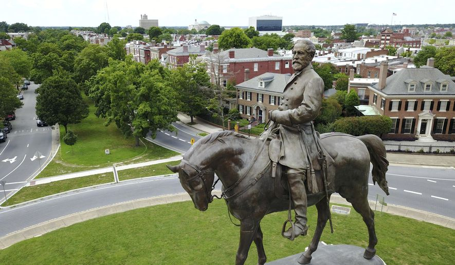 This Tuesday, June 27, 2017, file photo shows the statue of Confederate General Robert E. Lee that stands in the middle of a traffic circle on Monument Avenue in Richmond, Va.  A Virginia judge on Monday, Aug. 3, 2020, dissolved one injunction but imposed another preventing Virginia's governor from removing an enormous statue of Confederate Gen. Robert E. Lee. (AP Photo/Steve Helber, File)