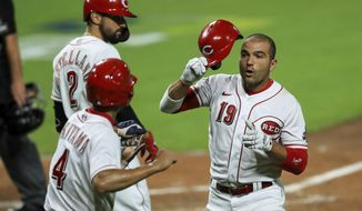 Cincinnati Reds' Joey Votto (19) is congratulated by teammates after hitting a two-run home run in the sixth inning of the team's baseball game against the Cleveland Indians in Cincinnati, Monday, Aug. 3, 2020. (AP Photo/Aaron Doster)
