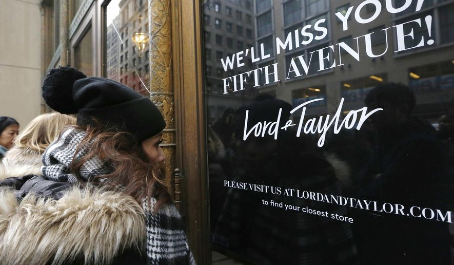 In this Jan. 2, 2019, file photo, women peer in the front door of Lord & Taylor's flagship Fifth Avenue store, which closed for good in New York. New York landmark retailer Lord & Taylor has filed for bankruptcy, joining a growing list of retailers flummoxed by the pandemic. (AP Photo/Kathy Willens, File)