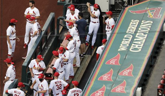 In this July 24, 2020, file photo, members of the St. Louis Cardinals wait to be introduced before the start of a baseball game against the Pittsburgh Pirates in St. Louis. The Cardinals 4-game series against the Detroit Tigers was postponed Monday, Aug. 3, 2020, after more Cardinals players and staff staffers test positive for COVD-19. The series was to have been played in Detroit from Tuesday through Thursday. (AP Photo/Jeff Roberson) ** FILE **