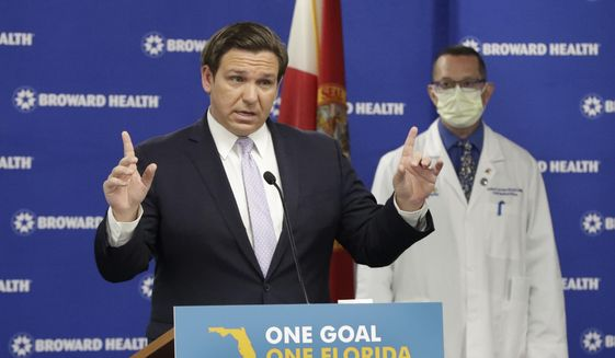 """Florida Gov. Ron DeSantis, left, speaks during a news conference along with Dr. Joshua Lenchus, right rear, chief medical officer of Broward Health Medical Center, Monday, Aug. 3, 2020, at the Broward Health Corporate Office in Fort Lauderdale, Fla. The number of patients in Florida hospitals for COVID-19 was relatively stable, at just below 8,000 and down from highs above 9,500 nearly two weeks ago. """"We are encouraged by some of the trends we are seeing,"""" DeSantis said Monday. (AP Photo/Wilfredo Lee)"""