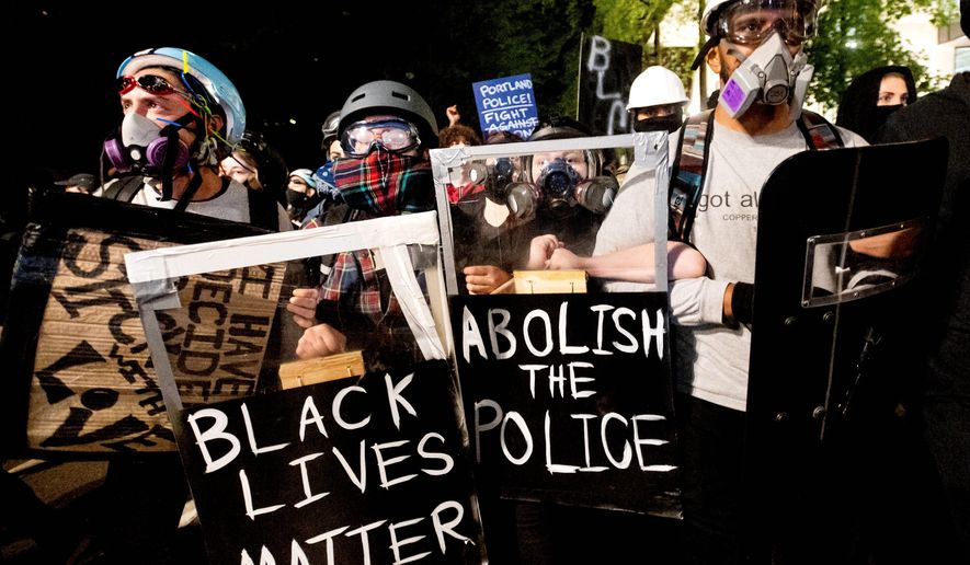 Black Lives Matter protesters march through Portland, Oregon, after rallying at the Mark O. Hatfield United States Courthouse on Sunday. Marches near the federal courthouse have calmed down while protests have migrated east across the Willamette River. (Associated Press)
