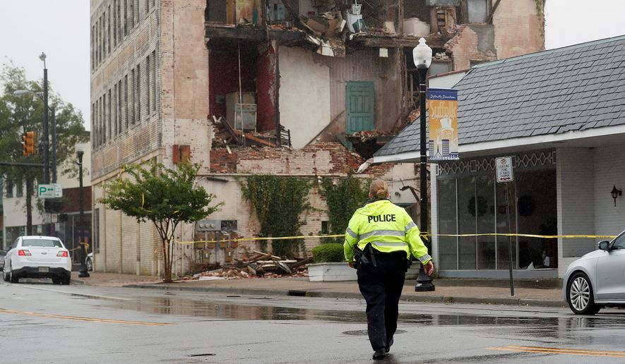 Suffolk Police survey damage to a building along Saratoga Street in Suffolk, Virginia, after Tropical Storm Isaias moved through the region Tuesday. The area experienced heavy rains and winds from the storm. (The Daily press viA Associated Press)