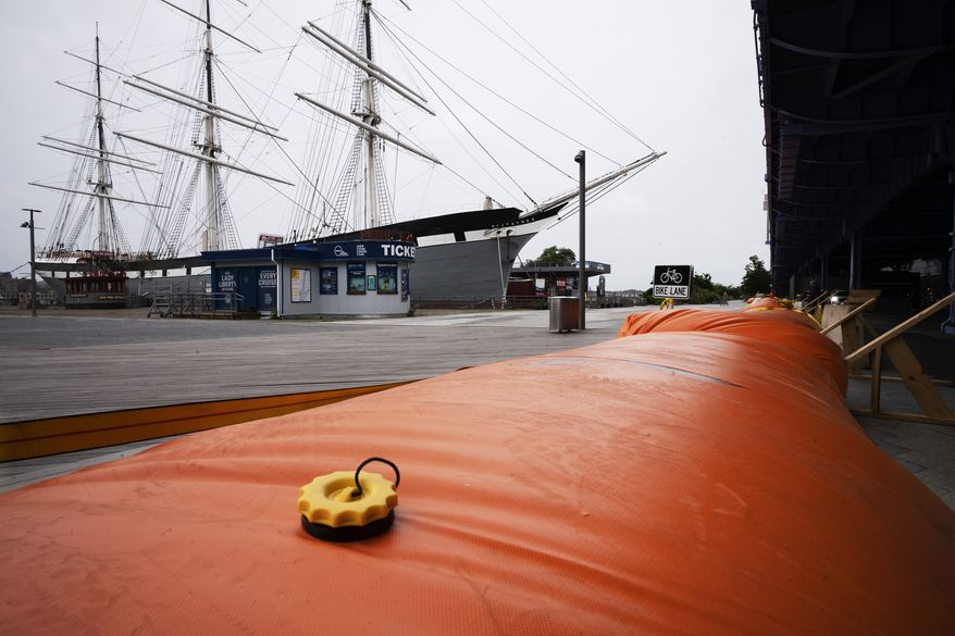 Water-filled rubber barricades protect the South Street Seaport from flooding, Tuesday, Aug. 4, 2020, in New York. Heavy rains are falling as Tropical Storm Isaias roars north on the Atlantic Coast, leaving behind power outages and reports of tornadoes. (AP Photo/Mark Lennihan)