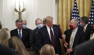 """Sen. Lamar Alexander, R-Tenn., gives President Donald Trump a walking stick during a signing ceremony for H.R. 1957 – """"The Great American Outdoors Act,"""" in the East Room of the White House, Tuesday, Aug. 4, 2020, in Washington. (AP Photo/Alex Brandon)"""