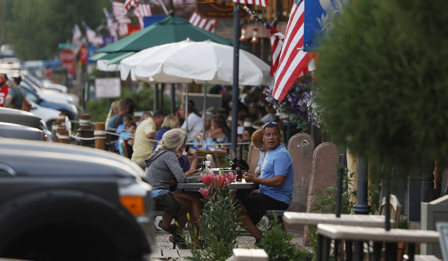 Diners eat outside a restaurant Tuesday, Aug. 4, 2020, in Grand Lake, Colo., during the coronavirus pandemic. (AP Photo/David Zalubowski)