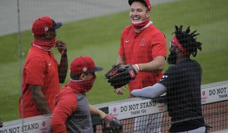 Los Angeles Angels center fielder Mike Trout, second from right, talks with Brian Goodwin, right, and other teammates before a baseball game against the Seattle Mariners, Tuesday, Aug. 4, 2020, in Seattle. (AP Photo/Ted S. Warren)