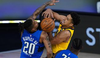 Indiana Pacers guard Malcolm Brogdon (7) and Orlando Magic guard Markelle Fultz (20) fight for a rebound during the second half of an NBA basketball game Tuesday, Aug. 4, 2020 in Lake Buena Vista, Fla. (AP Photo/Ashley Landis)