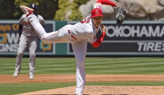 Los Angeles Angels pitcher Shohei Ohtani, right, of Japan, follows through as Houston Astros' Yuli Gurriel leads off during the second inning of a baseball game Sunday, Aug. 2, 2020, in Anaheim, Calif. (AP Photo/Mark J. Terrill)