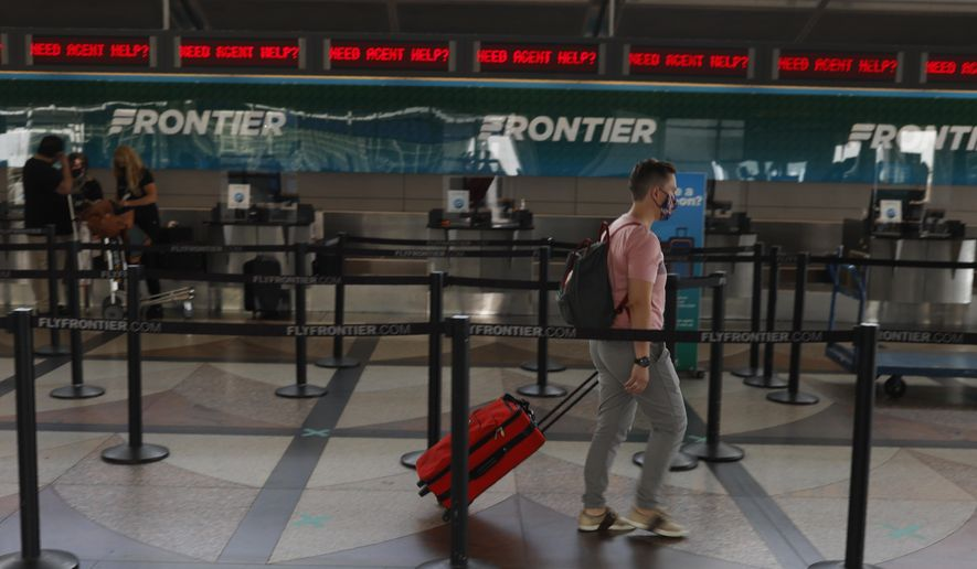 A lone traveler heads to the ticketing counter of Frontier Airlines in the main terminal of Denver International Airport on July 22, 2020, in Denver. (AP Photo/David Zalubowski, File)