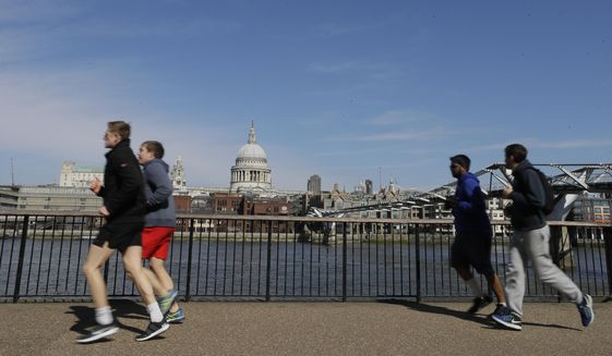 FILE - In this file photo dated  Sunday, March 22, 2020, people run to keep fit along the south bank of the River Thames in London.  European Union regulators have said Tuesday Aug, 4, 2020, they're opening an in-depth investigation into U.S. tech giant Google's plan to buy fitness tracking device maker Fitbit. (AP Photo/Kirsty Wigglesworth, FILE)