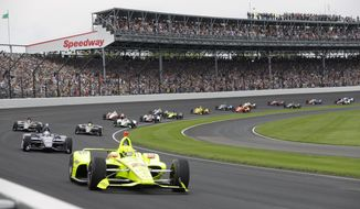 """FILE - In this May 26, 2019, file photo, Simon Pagenaud, of France, leads the field through the first turn on the start of the Indianapolis 500 IndyCar auto race at Indianapolis Motor Speedway in Indianapolis. Roger Penske has reversed course and decided not to allow fans at the Indianapolis 500 later this month. The 104th running of """"The Great American Race"""" will be the first without spectators, who showed up at Indianapolis Motor Speedway every year, even during the Great Depression. (AP Photo/Darron Cummings, File)"""