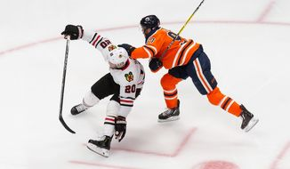 Edmonton Oilers' Connor McDavid (97) works against Chicago Blackhawks' Brandon Saad (20) during the second period of an NHL hockey playoff game Monday, Aug. 3, 2020, in Edmonton, Alberta. (Codie McLachlan/The Canadian Press via AP)