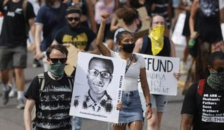 In this June 27, 2020, file photo, demonstrators carry placards as they walk down Sable Boulevard during a rally and march over the death of Elijah McClain in Aurora, Colo. (AP Photo/David Zalubowski, File)