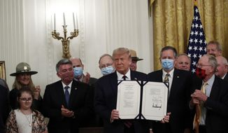 """President Donald Trump poses for a photo during a signing ceremony for H.R. 1957 – """"The Great American Outdoors Act,"""" in the East Room of the White House, Tuesday, Aug. 4, 2020, in Washington. (AP Photo/Alex Brandon)"""