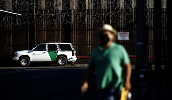 A Border Patrol vehicle sits near the border wall separating Mexicali, Mexico from Calexico, Calif., Tuesday, July 21, 2020, in Calexico. The city of 1 million just to the south brings tens of thousands of people daily to cross. Janette Angulo, Imperial County's public health director, estimates the population doubles during the day in winter, making the official count deceptively low. (AP Photo/Gregory Bull)