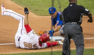 New York Mets shortstop Andres Gimenez, back center, tags out Washington Nationals Juan Soto as Soto tries to steal third base during the fourth inning of a baseball game in Washington, Wednesday, Aug. 5, 2020. (AP Photo/Manuel Balce Ceneta)