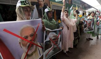 Women hold crossed out portrait of Indian Prime Minister Narendra Modi as they participate in a train march to mark the first anniversary of India's decision to revoke the disputed region's semi-autonomy, in Karachi, Pakistan, Wednesday, Aug. 5, 2020. Last year on Aug. 5, India's Hindu-nationalist-led government of Prime Minister Modi scrapped its separate constitution and removed inherited protections on land and jobs. (AP Photo/Fareed Khan)