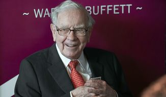 In this May 5, 2019, file photo Warren Buffett, Chairman and CEO of Berkshire Hathaway, smiles as he plays bridge following the annual Berkshire Hathaway shareholders meeting in Omaha, Neb. Buffett's company has purchased another $400 million of Bank of America stock less than a week after buying roughly $800 million of the bank's stock. Berkshire Hathaway Inc. said Monday, July 27, 2020 it held 998 million Bank of America shares after the latest purchases, which represents roughly 11.5% of the bank's stock. (AP Photo/Nati Harnik, File)