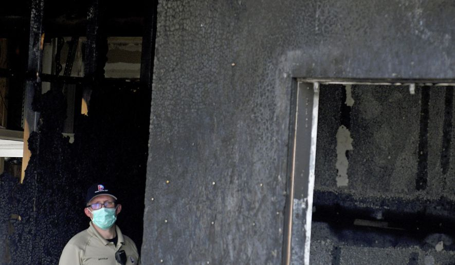 An investigator stands in the doorway of a home in suburban Denver on Wednesday, Aug. 5, 2020, where five people were found dead after a fire. Three people escaped the fire by jumping from the home's second floor. Investigators believe the victims were a toddler, an older child and three adults. Authorities suspect was intentionally set. Witnesses told firefighters that three people on the second floor of the burning home jumped to safety. A fire department spokesman said the fire's heat pushed back a police officer trying to rescue the people who were on the home's first floor. (AP Photo/Thomas Peipert)