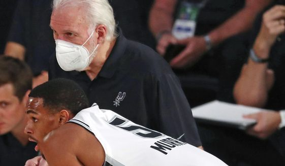 San Antonio Spurs head coach Gregg Popovich in a mask talks with guard Dejounte Murray (5) during the first half of an NBA basketball game, Friday, July 31, 2020, in Lake Buena Vista, Fla. (Kim Klement/Pool Photo via AP)  **FILE**