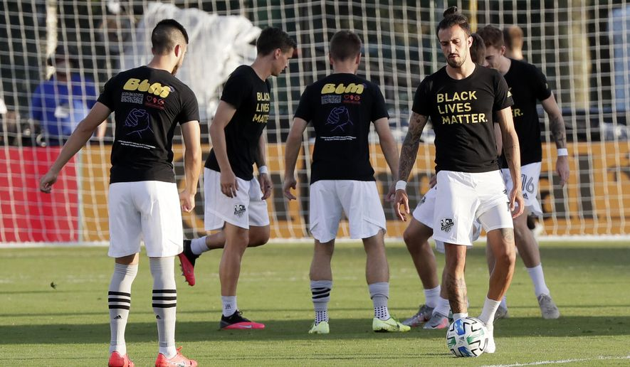 Montreal Impact players warm up wearing Black Lives Matter t-shirts before an MLS soccer match against Orlando City, Saturday, July 25, 2020, in Kissimmee, Fla. (AP Photo/John Raoux)