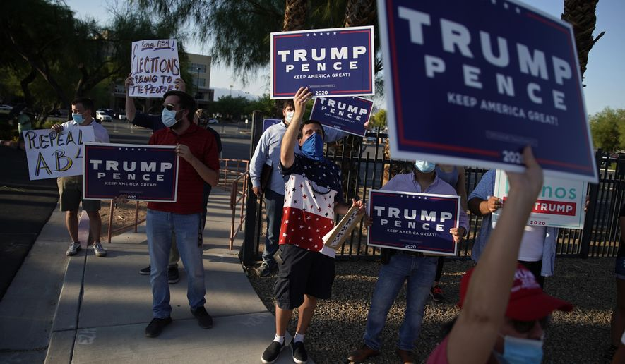 In this file photo from Aug. 4, 2020, people protest in Las Vegas against a law signed this week by Nevada Gov. Steve Sisolak to mail ballots to all of the state's active voters ahead of the November election. Two planned Trump reelection campaign rallies will not be able to move forward thanks to new restrictions put in place by Mr. Sisolak. (AP Photo/John Locher)  **FILE**