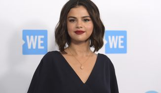 """FILE - Selena Gomez arrives at WE Day California on April 19, 2018, in Inglewood, Calif. Gomez is taking the heat in the kitchen. The singer-actress slices and dices in """"Selena + Chef,"""" debuting Aug. 13 on the new HBO Max streaming service. The 10-episode series was shot in the kitchen of Gomez's new Los Angeles-area house. Her grandparents and two friends, who have been quarantining with her, serve as taste testers. (Photo by Richard Shotwell/Invision/AP, File)"""