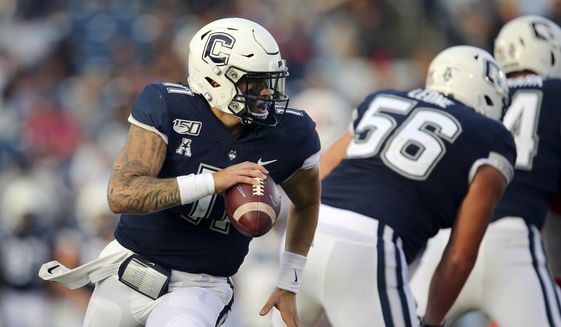 In this Sept. 7, 2019, file photo, Connecticut quarterback Jack Zergiotis (11) rolls out of the pocket during an NCAA football game against Illinois in East Hartford, Conn.  UConn has canceled its 2020-2021 football season, becoming the first FBS program to suspend football because of the coronavirus pandemic. (AP Photo/Stew Milne, File)  **FILE**