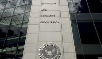 FILE - This Saturday, Aug. 5, 2017, file photo shows the U.S. Securities and Exchange Commission building in Washington. Securities regulators are investigating three hotel companies, Wednesday, Aug. 5, 2020,  that returned tens of millions in federal virus-relief money for transactions going back to 2018. The companies controlled by Dallas hotelier Monty Bennett came under scrutiny after taking tens of millions of dollars from a fund designed to help small businesses survive the pandemic.  (AP Andrew Harnik, File)