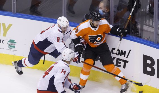 Washington Capitals defenseman Dmitry Orlov (9) and Philadelphia Flyers defenseman Robert Hagg (8) vie for the puck in the cornerduring the second period of an NHL hockey playoff game  Thursday, Aug. 6, 2020, in Toronto. (Cole Burston/The Canadian Press via AP)