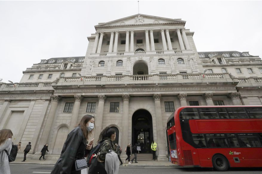 FILE - In this Wednesday, March 11, 2020 file photo, pedestrians wearing face masks pass the Bank of England in London. The Bank of England left its benchmark interest rate at a record low of 0.1% on Thursday Aug. 6, 2020, as it expressed caution about how rapidly the United Kingdom's economy will recover from the COVID-19 pandemic. (AP Photo/Matt Dunham, File)